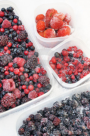 Plastic containers of frozen mixed berries in snow