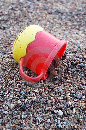Plastic cup on sand