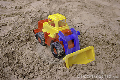 Plastic toy tractor on the sand