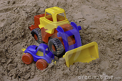 Plastic toy tractor on the sand with the car