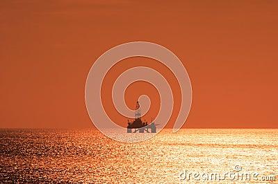 Plataforma petrolífera a pouca distância do mar durante o por do sol