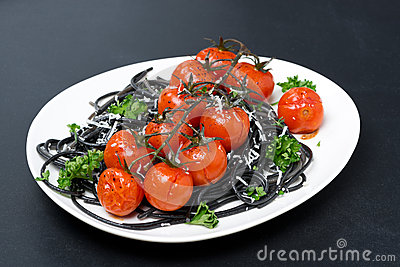 Plate of black pasta with baked tomatoes, parmesan cheese