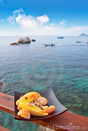 Plate with exotic fruits against sea view