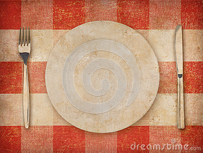 Plate, fork, knife over grunge tablecloth background