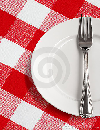 Plate and fork on table with checked tablecloth