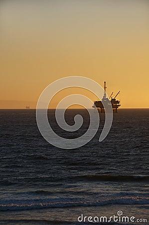 Plate-forme pétrolière au coucher du soleil.
