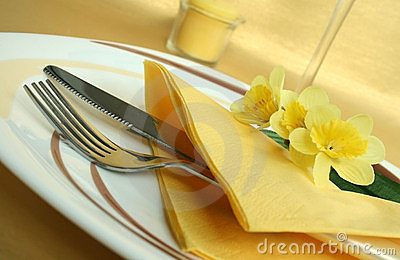 Plate with knife and fork on yellow tablecloth
