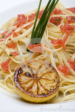 Plate of linguine topped with diced tomatos