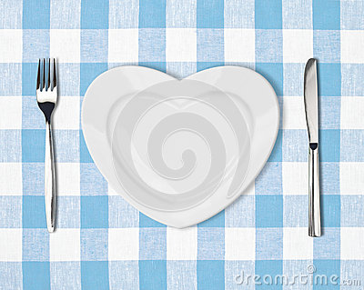 Plate in shape of heart, table knife and fork on blue tablecloth