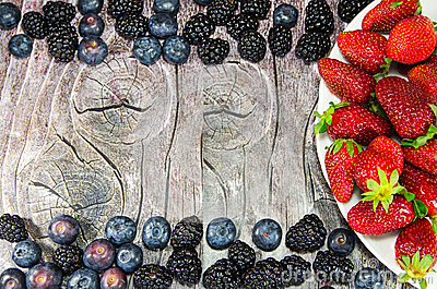 Plate with strawberries on wood with empty space for advertisement