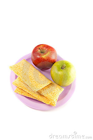 A plate with two apple  and crisps