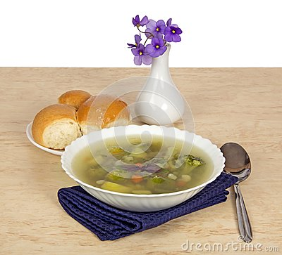 Plate of vegetable soup and violets