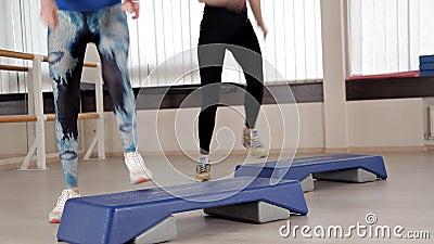 Plates-formes d'?tape Filles dans des chaussures de sports faisant des exercices pour l'a?robic Le concept du serrage dans le gym clips vidéos