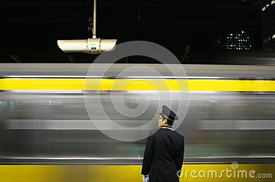 Platform worker watches train arriving at station  Editorial Image