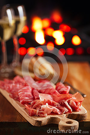 Platter of serrano jamon Cured Meat with cozy fireplace and wine