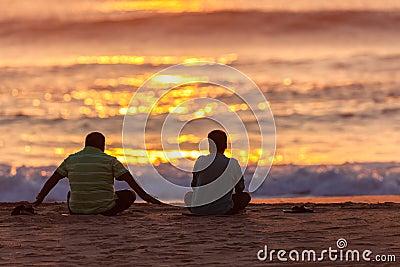 Playa asiática de los varones de la salida del sol dos asentada Fotografía editorial