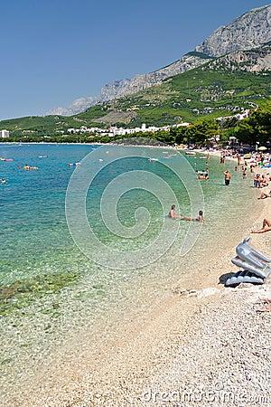 Playa asombrosa con la gente en Tucepi, Croacia Foto editorial