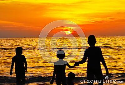 Playa de la puesta del sol con los niños jovenes