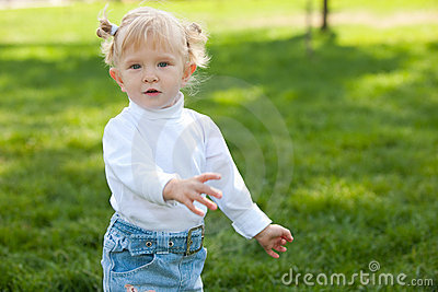 Playful blond little girl walking in the park