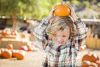 Playful Boy Holding His Pumpkin at a Pumpkin Patch