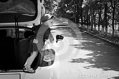 Playful boy standing in the open truck of a car