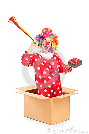 Playful clown coming out of a box and holding a horn and a prese