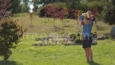 Playful father throwing infant son in the air stock footage
