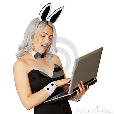Playful girl dressed as a rabbit with a laptop