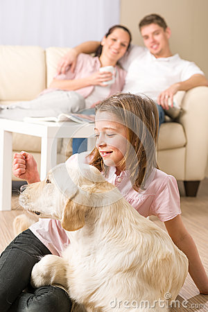 Playful girl petting family dog with parents