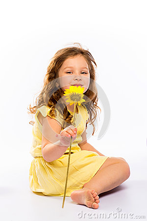 Playful little girl in yellow dress smiling
