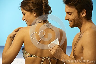 Playful man putting sun cream on woman in swimsuit