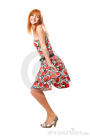 Playful red-haired girl in a dress
