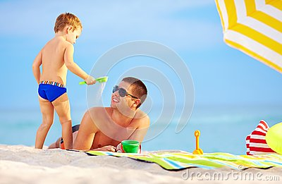 Playful son strews sand on father, beach