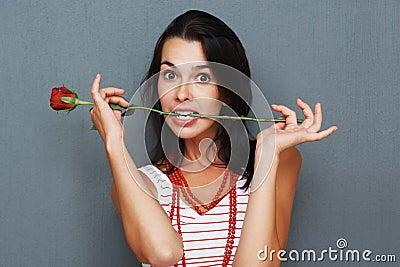 Playful woman posing with rose between teeth