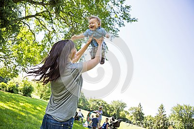 Playful Young Mother Lifting Baby Boy At Park