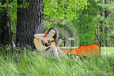 Teenage Girl Playing Guitar In Woods