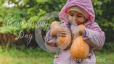 Playing outdoors cute little girl holding a pumpkin. Harvest of pumpkins, the lovely girl and large pumpkins. Thanksgiving day Stock Photo