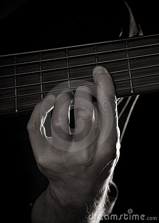 Playing six-string electric bass guitar