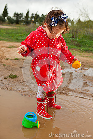 Free Playing With Her Water Toys On Muddly Puddles Royalty Free Stock Photography - 45623577