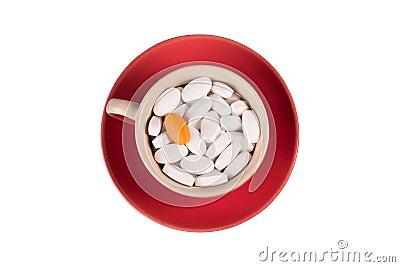 Píldoras en una taza en un platillo rojo