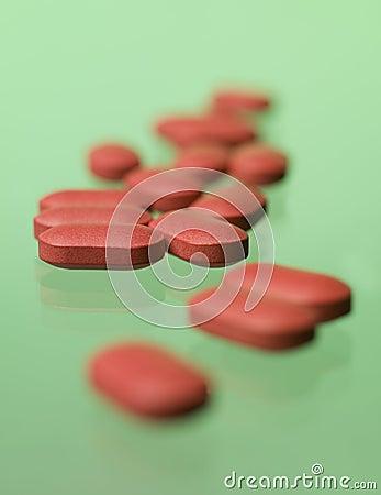 Píldoras rojas hacia fondo verde