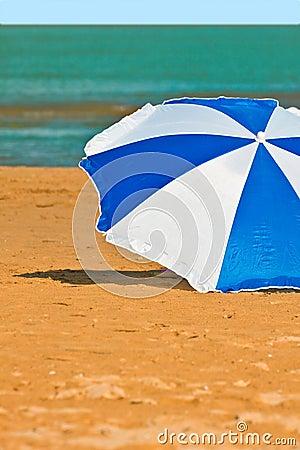 Pleasant sitting under a colorful umbrella on b