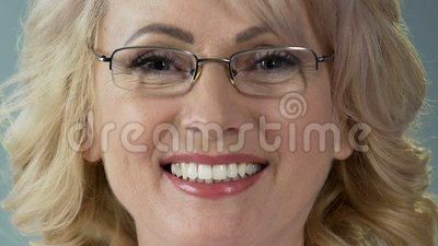 Pleased senior female patient smiling after teeth whitening procedure, closeup. Stock footage stock video footage