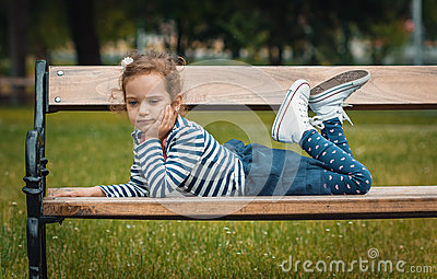 Pleasure little girl lying on bench