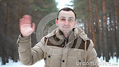 Plenerowy portret przystojny mężczyzna w kurtce wita przy kamerą zdjęcie wideo