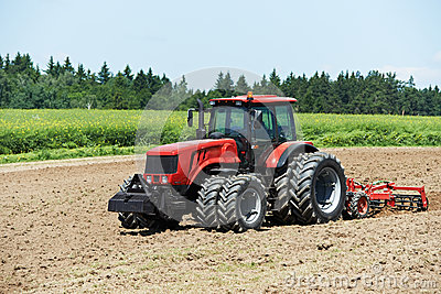 Ploughing tractor at field cultivation work