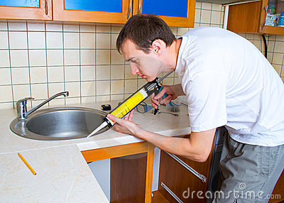 Plumber putting a silicone sealant