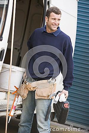 Plumber standing with van