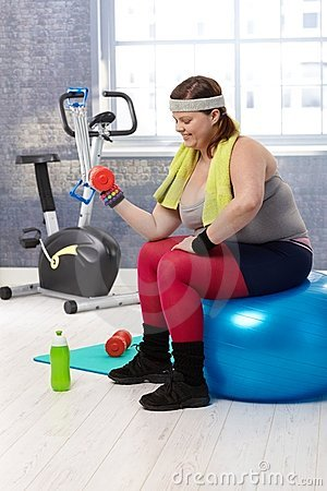 Plump woman exercising with dumbbells