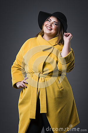 Free Plus Size Fashion Model In Yellow Coat And Black Hat, Fat Woman On Gray Background, Overweight Female Body Stock Photo - 91232500